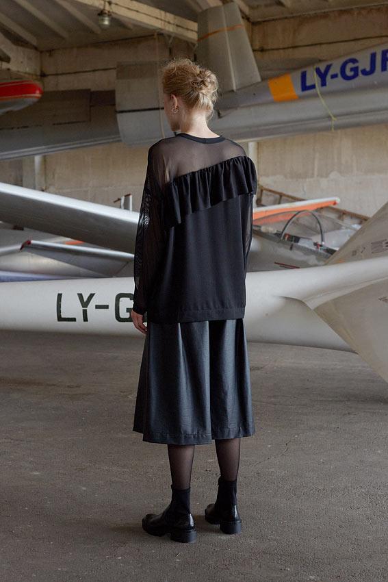 Model wearing black shiny wide leg culottes back view