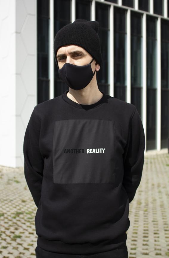 Modelis dėvi juodą laisvo kirpimo džemperį su juodu užsiūtu kvadratu ir printu jame