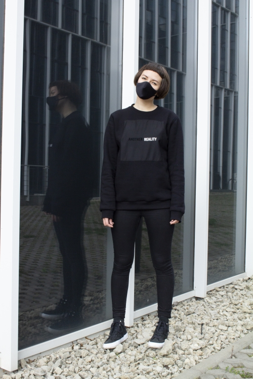 Modelis dėvi juodą unisex džemperį su užrašu another reality