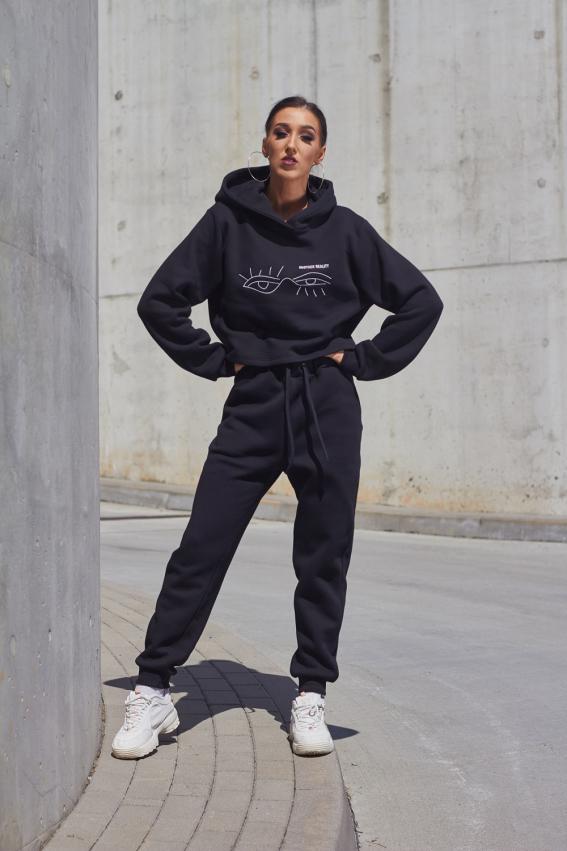 Modelis dėvi juodas laisvalaikio kelnes