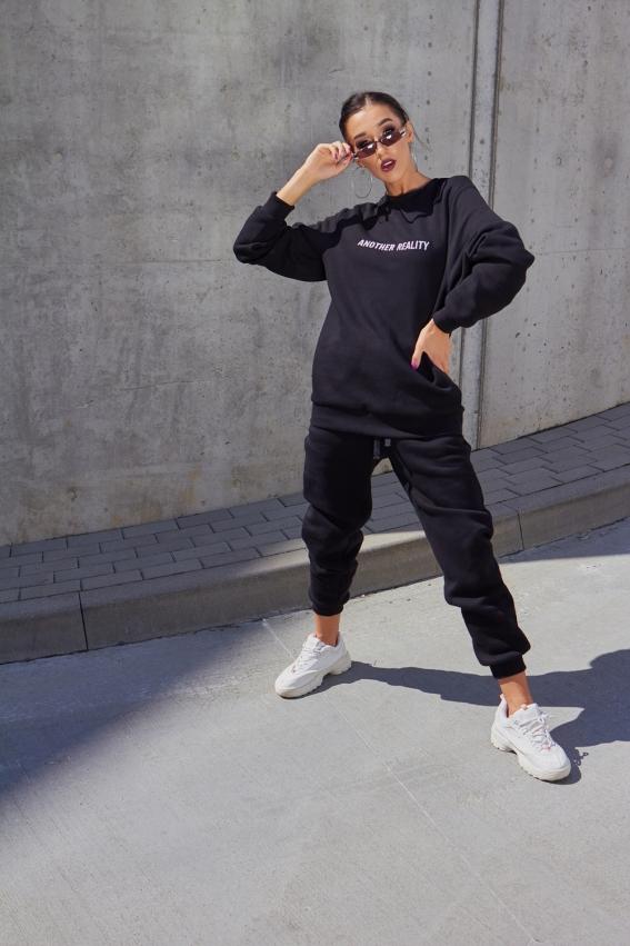 Modelis dėvi juodą unisex tipo džemperį su priekyje siuvinėtu another reality užrašu