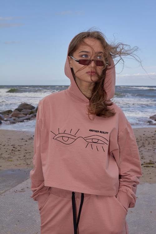 Modelis dėvi rožinį džemperį su juodu akių siuvinėjimu