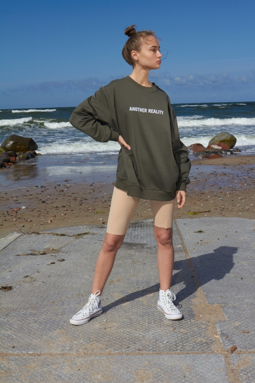 Model is wearing khaki unisex embroidered sweatshirt