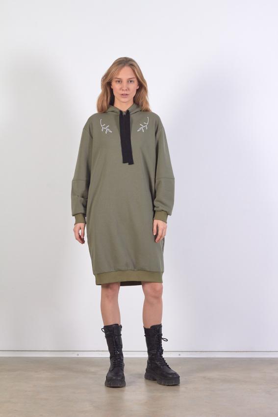 Modelis dėvi chaki spalvos džemperio tipo suknelę su gobtuvu ir baltu lapų siuvinėjimu priekyje