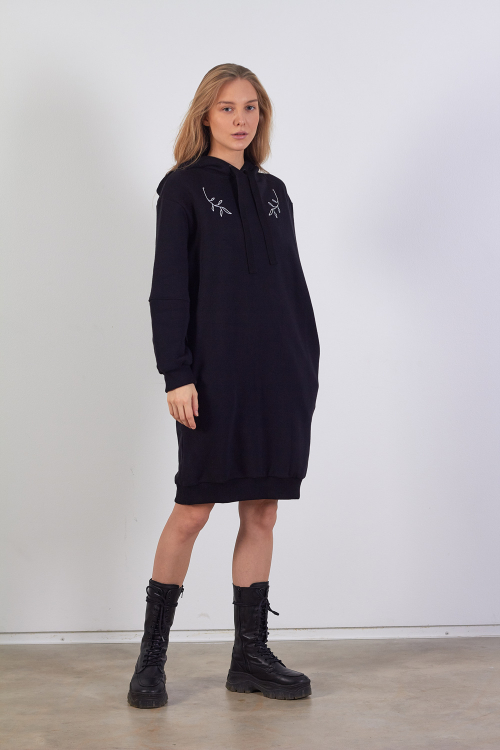 Model is wearing black sweatshirt dress