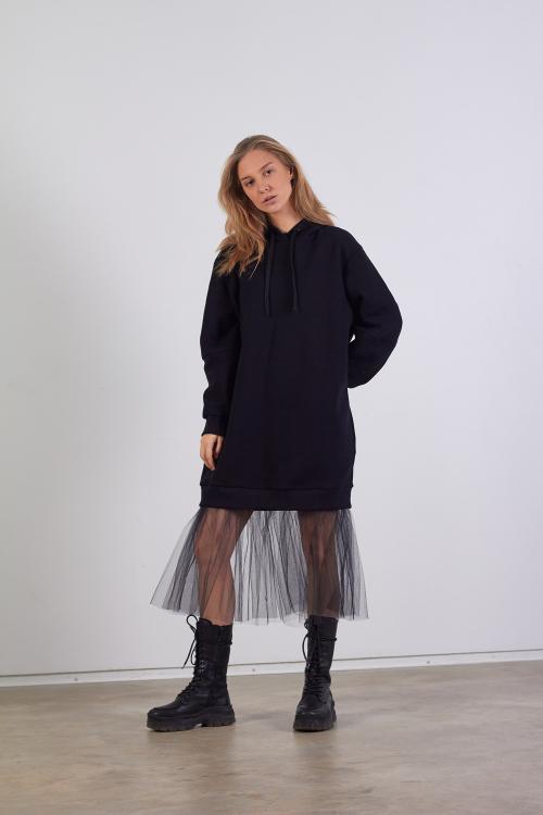 Modelis dėvi juodą dzemperio tipo suknelę su tiuliu