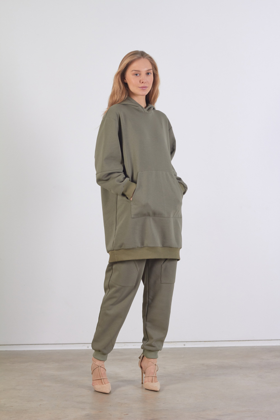 Modelis dėvi ilgą chaki spalvos džemperį su kišene priekyje ir dideliu gobtuvu