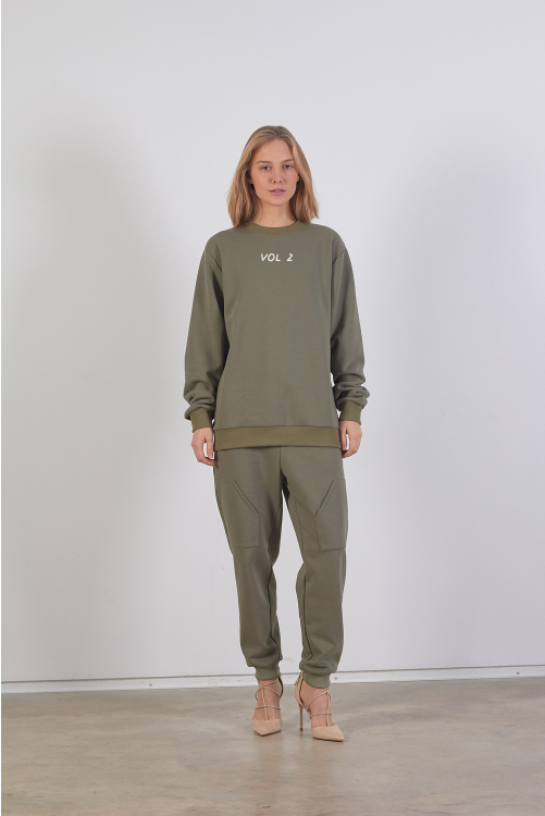 Model is wearing unisex embroidered khaki sweatshirt