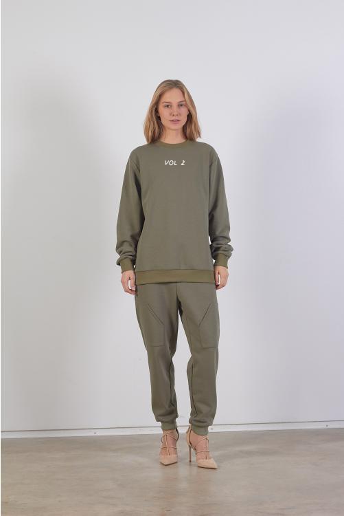 Modelis dėvi Unisex khaki džemperį su siuvinėjimu priekyje