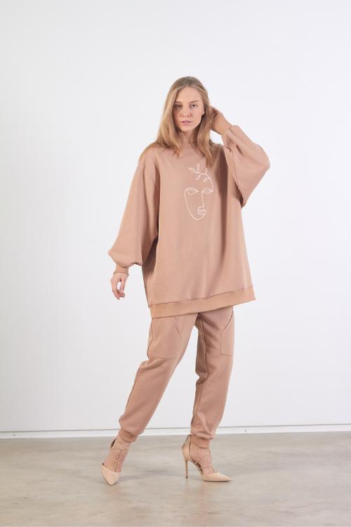 Modelis dėvi vieno sysžio smėlio spalvos džemperį su baltu siuvinėjimu priekyje