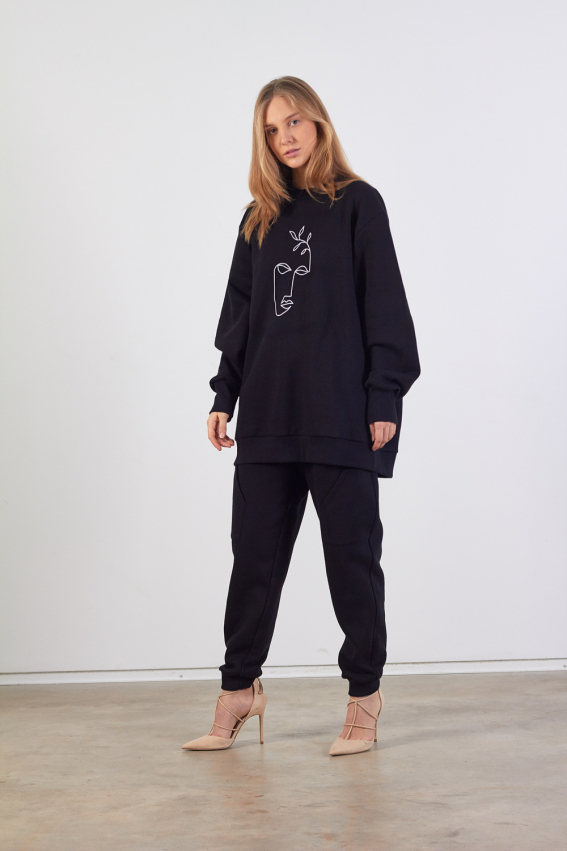 Vieno dydžio juodos spalvos džemperis su baltu veido siuvinėjimu priekyje