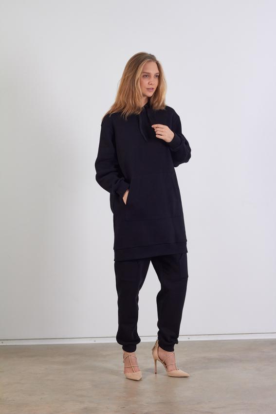 Modelis dėvi ilgą juodą džemperį su uždėtine kišene priekyje ir dideliu gobtuvu