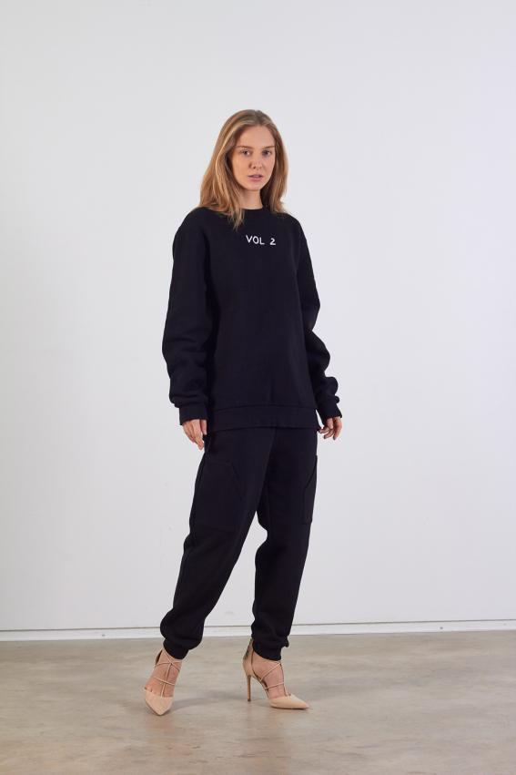 Modelis dėvi unisex tipo juodą džemperį su išsiuvinėtu užrašu priekyje