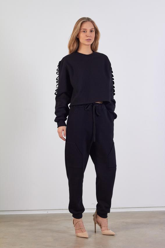Modelis dėvi patrumpintą moterišką juodą džemperį su dekoratyvinėm juostom užsiūtom ant rankovių