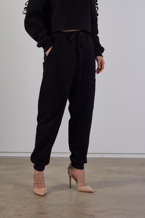 Modelis dėvi juodas moteriškas laisvalaikio kelnes su kišenėmis šonuose ir raišteliais.