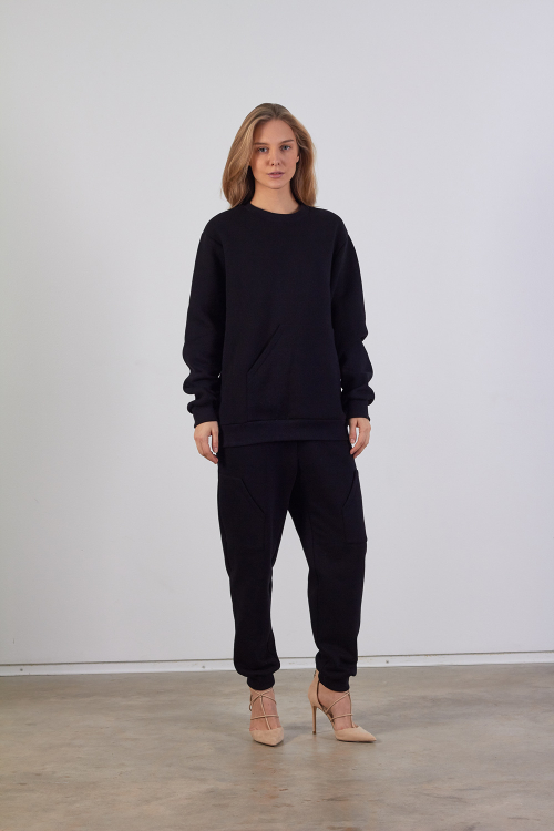 Model is wearing black unisex sweatshirt with asymmetrical pocket in front