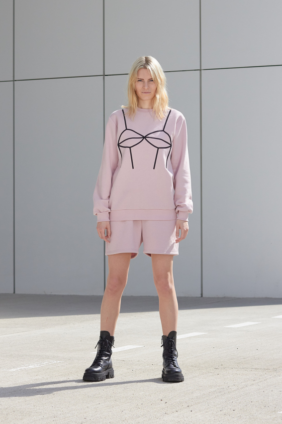 model is wearing pink sweatshirt with embroidery