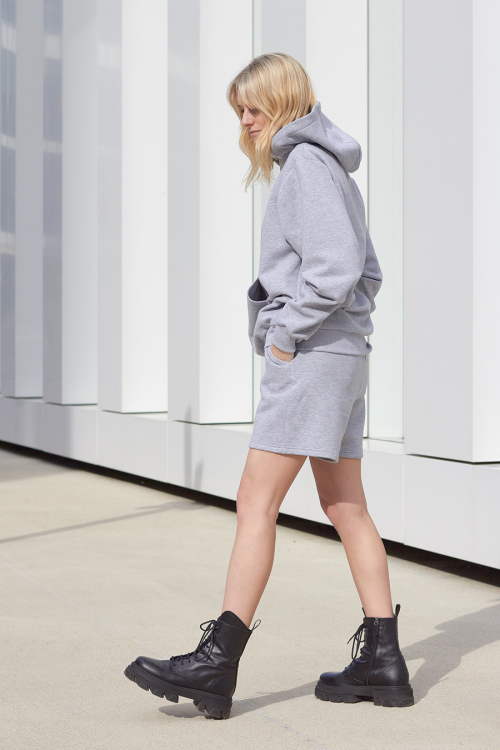 Model is wearing grey shorts and hoodie