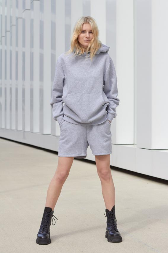 Model is wearing oversized grey hoodie