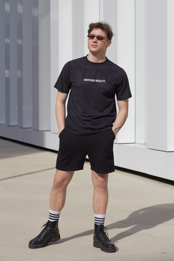 Model is wearing men's black shorts
