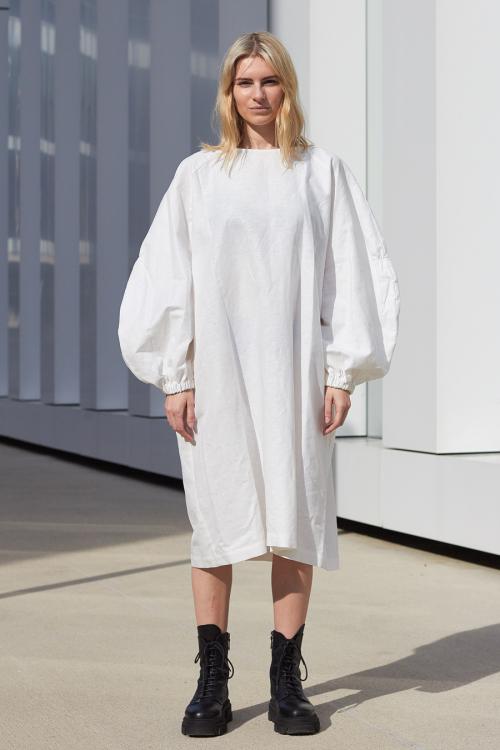 Model is wearing white linen os dress